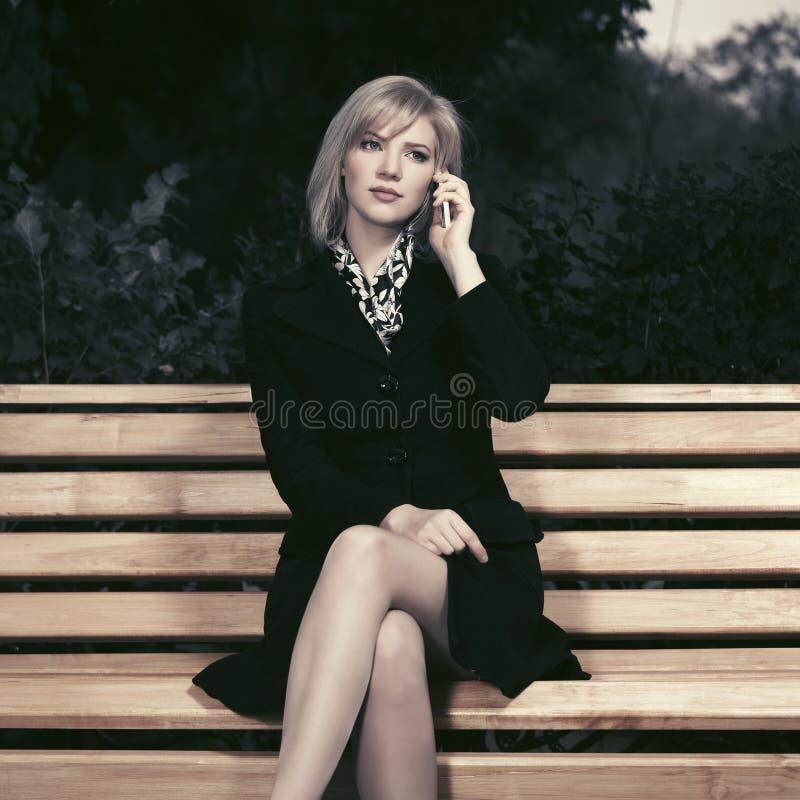 年轻时尚白肤金发的妇女谈话在手机坐长凳 免版税库存图片