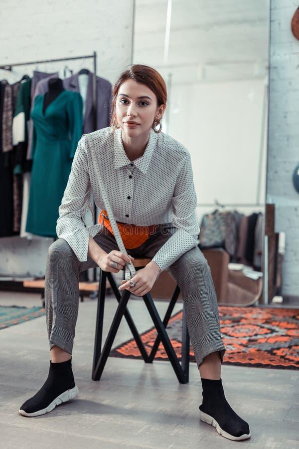 年轻时尚编辑坐在时尚精品店的椅子 免版税库存图片