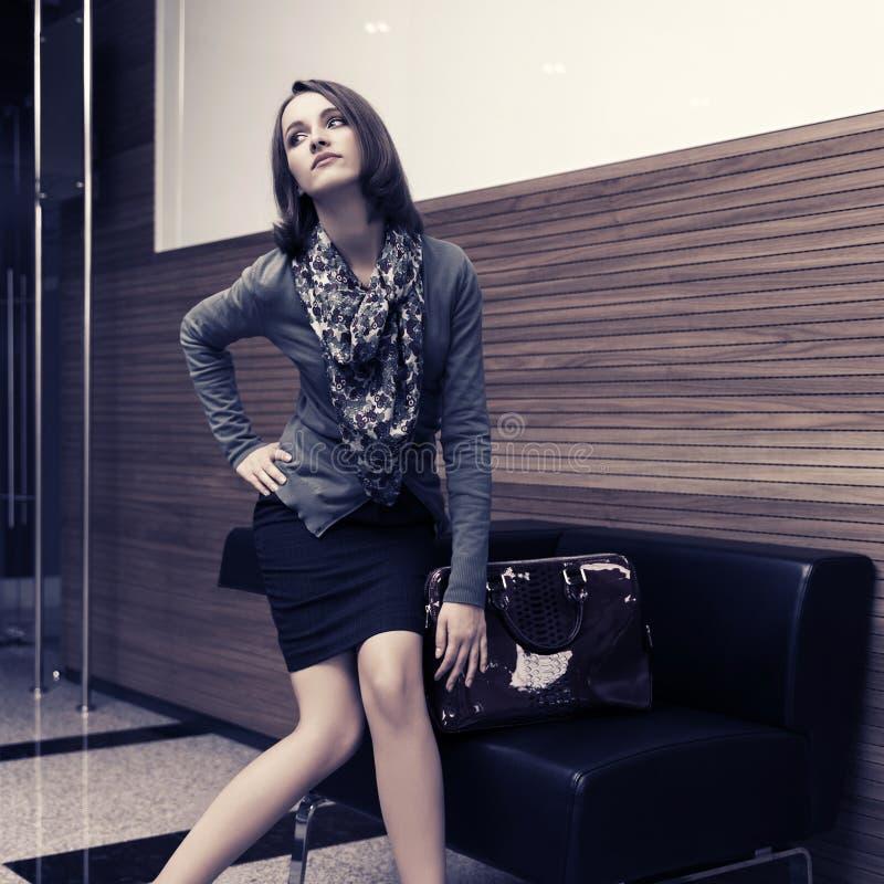 年轻时装业妇女坐在办公室内部的长沙发 库存照片