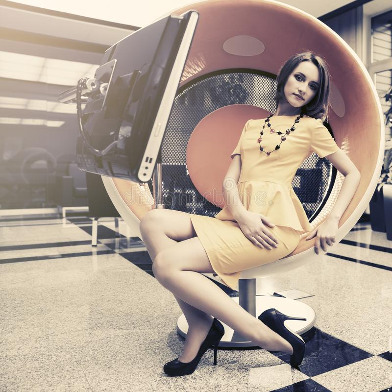 年轻时装业妇女坐计算机椅子在办公室 库存图片