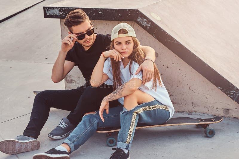 年轻时髦夫妇坐在与他们的longboards的晴朗的skatepark 库存照片