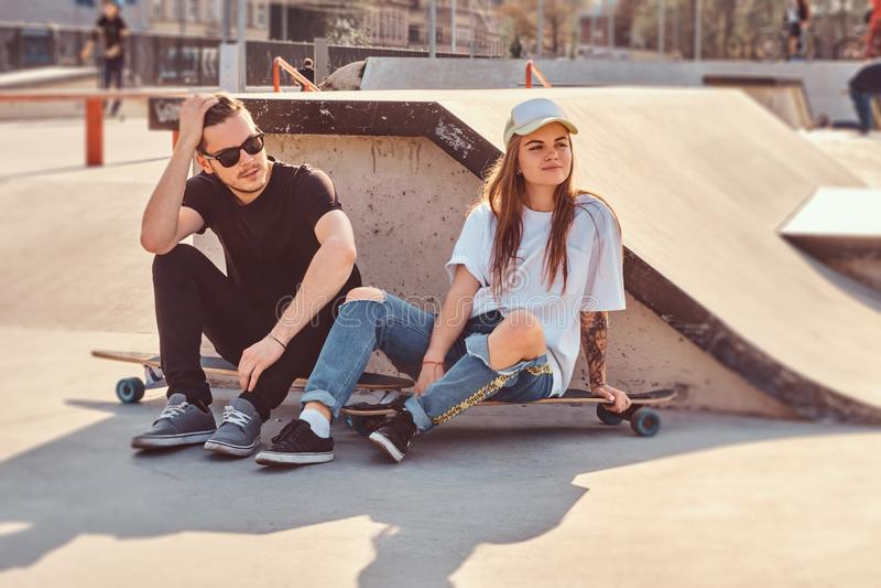 年轻时髦夫妇坐在与他们的longboards的晴朗的skatepark 免版税库存图片