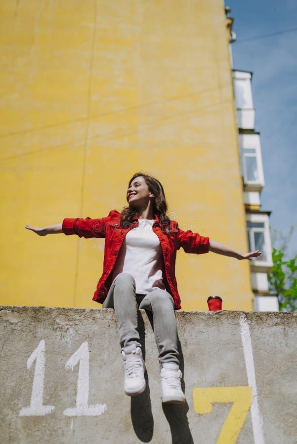 年轻时髦微笑的假装飞行在栏杆 免版税图库摄影