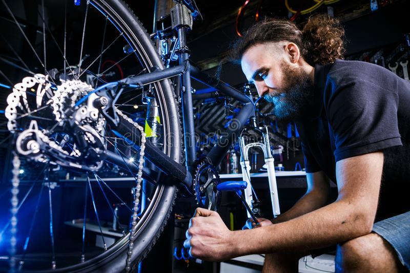 年轻时髦有胡子,与长的自行车车间的头发白种人男性技工工作者使用为修理Cranksets的一个工具 免版税库存照片