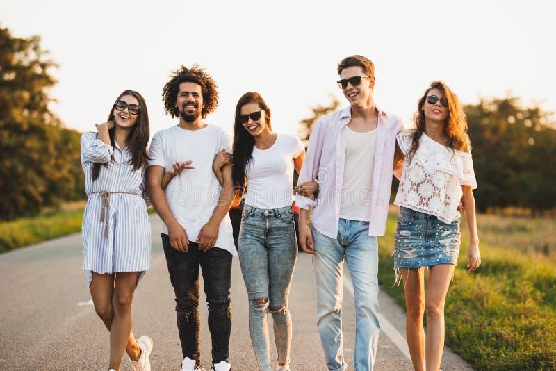 年轻时髦的两个人和三个女孩在一好日子握手并且走在路 免版税库存照片