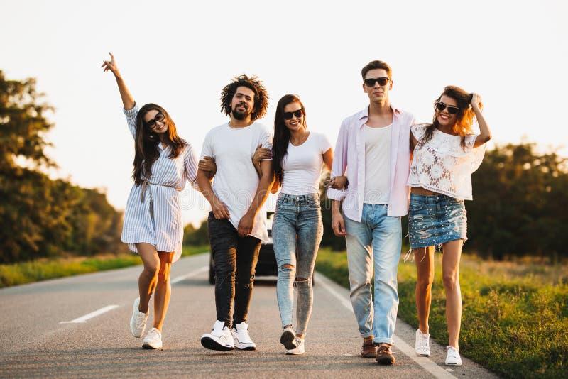 年轻时髦的两个人和三个女孩在一条乡下公路走在一好日子 库存图片