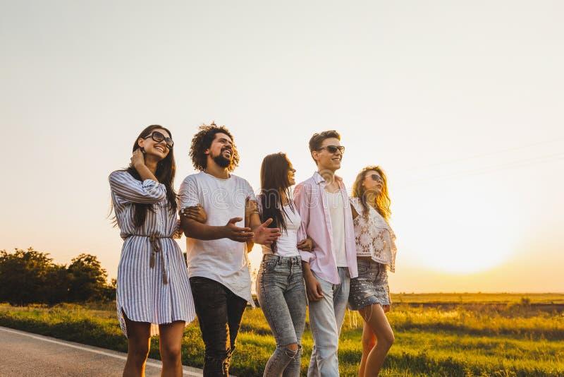 年轻时髦的两个人和三个女孩在一条乡下公路走在一好日子 免版税库存照片