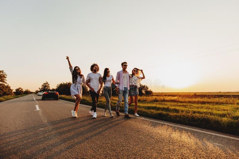 年轻时髦的两个人和三个女孩在一条乡下公路走在一好日子 免版税库存图片