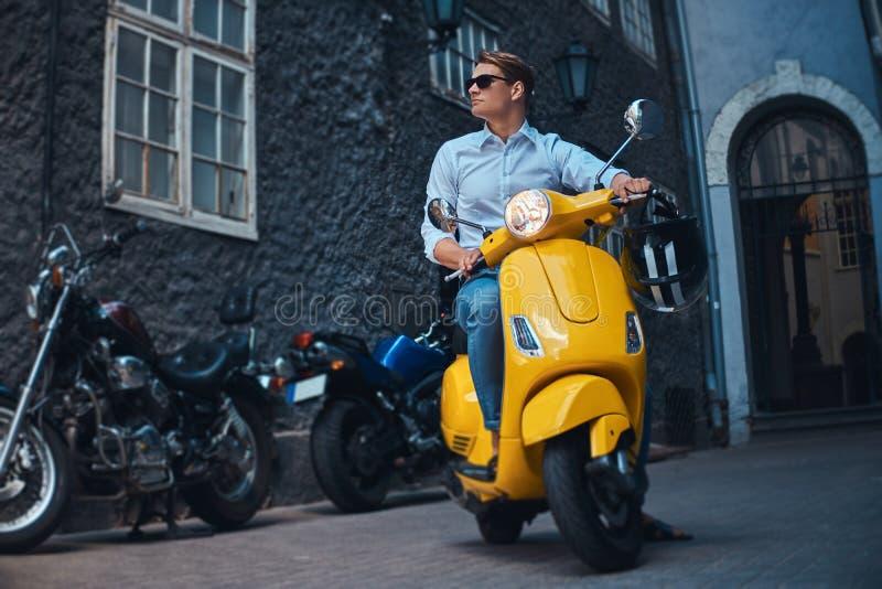 年轻时髦的人在一件白色衬衣的a穿戴了,并且牛仔裤在一条老欧洲街道上的黄色经典意大利滑行车乘坐 免版税库存照片
