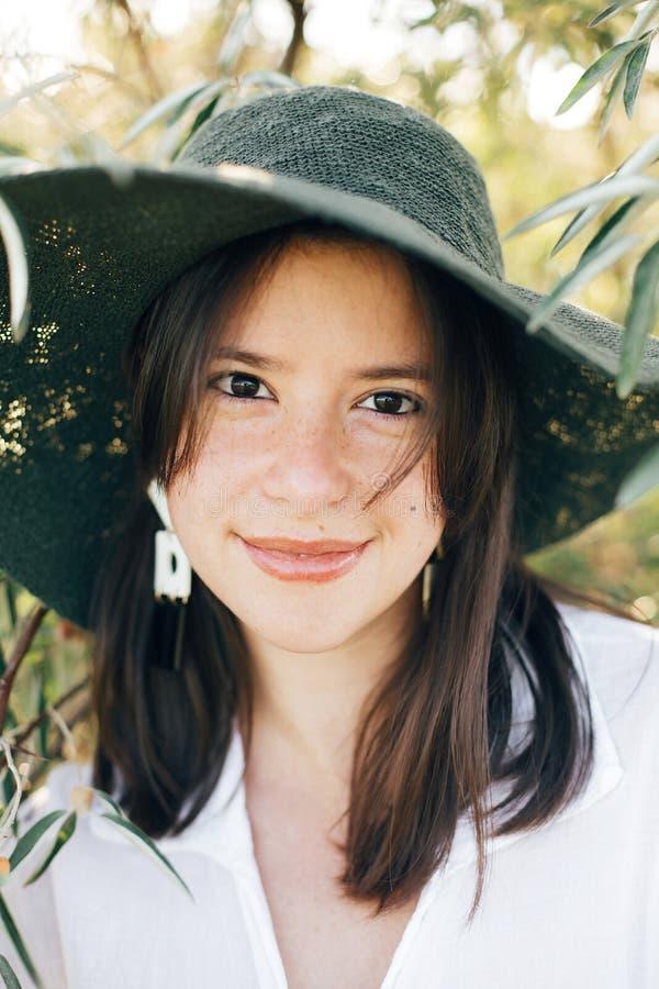 年轻时髦的女人画象有摆在在软的平衡的光,时髦的boho女孩的绿橄榄分支的现代耳环的 库存照片
