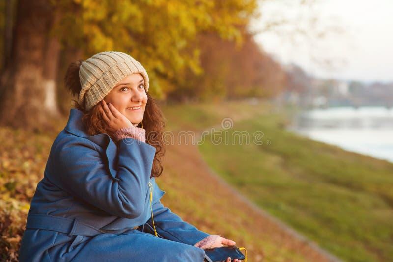 年轻时髦的妇女听在秋天步行的音乐 秋天假期 使用智能手机的年轻可爱的女孩户外 妇女打扮 免版税库存图片