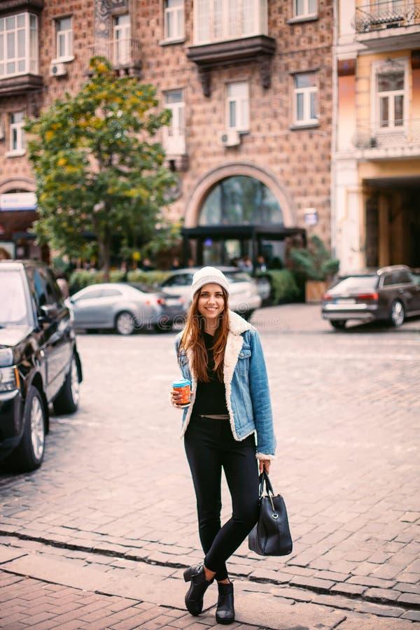 年轻时髦的红色头发女孩,通过Windows 佩带的时兴的玻璃和一件黑外套 保留咖啡 抽象看 免版税库存照片