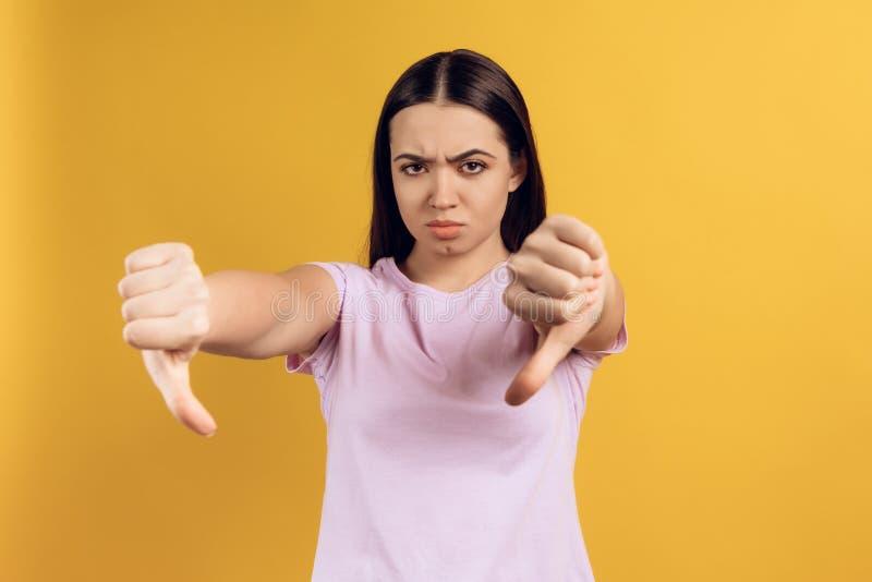 年轻普通的女孩显示姿态拇指下来 免版税库存照片