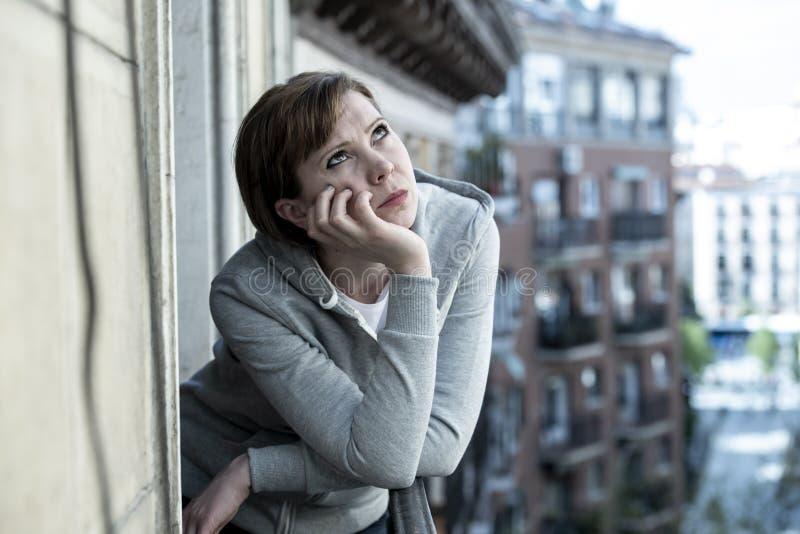 年轻有吸引力不快乐沮丧偏僻妇女看在阳台在家担心 都市视图 免版税库存图片