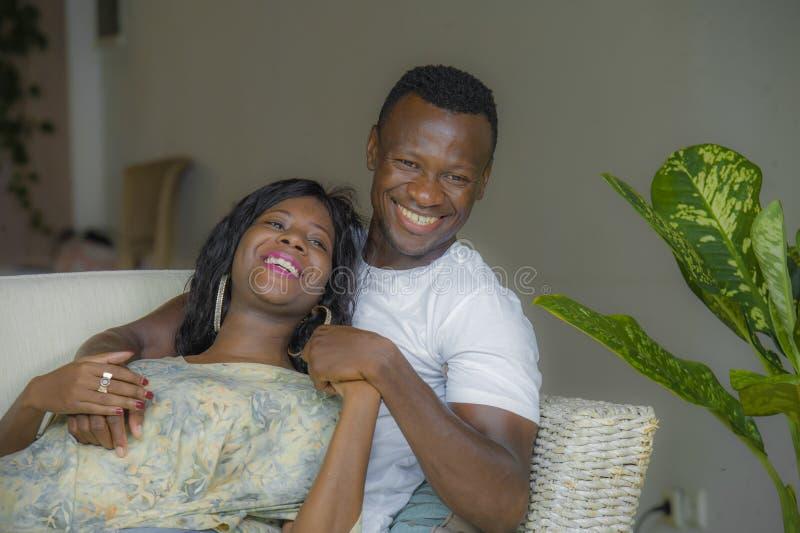 年轻有吸引力和愉快的黑非裔美国人的夫妇在家放松了微笑沙发长沙发谈的甜点一起享用和  免版税库存图片