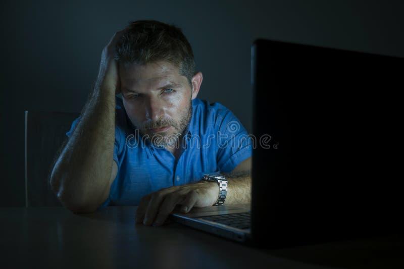 年轻有吸引力和疲乏不剃须人工作夜间在被挫败和被用尽的黑暗的感觉的手提电脑  免版税库存图片