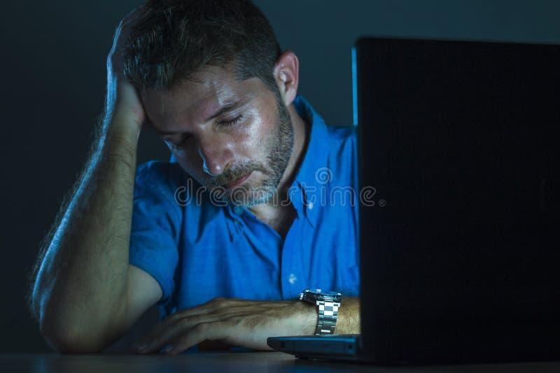 年轻有吸引力和疲乏不剃须人工作夜间在被挫败和被用尽的黑暗的感觉的手提电脑  库存照片