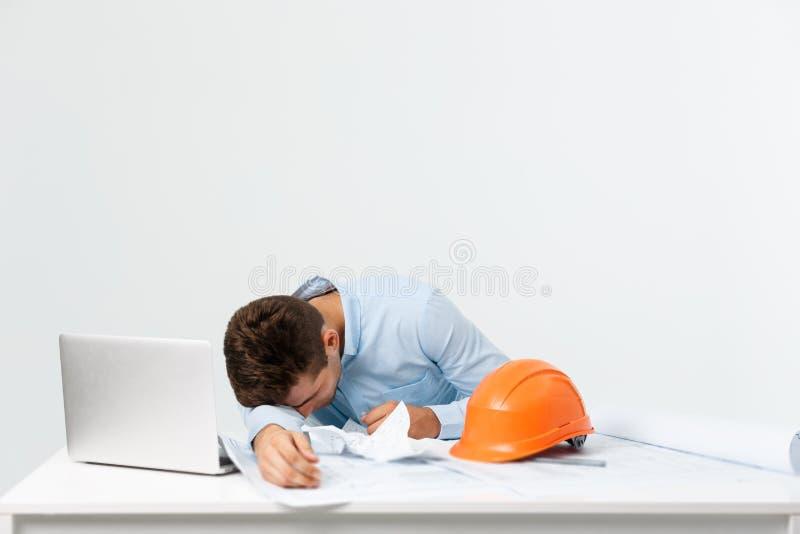 年轻有吸引力工程师人感觉在工作地点疲倦了 库存照片
