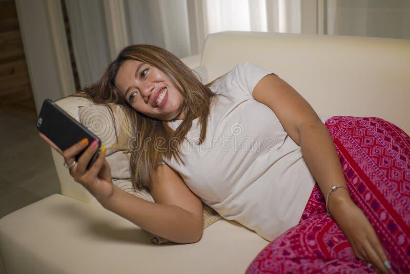 年轻有吸引力愉快和轻松学生女孩享用象家一样在客厅沙发长沙发使用互联网社会媒介或约会应用程序 免版税图库摄影