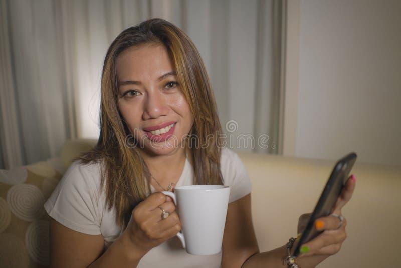 年轻有吸引力愉快和轻松西班牙妇女享用象家一样在客厅沙发长沙发使用互联网社会媒介或约会 免版税库存图片