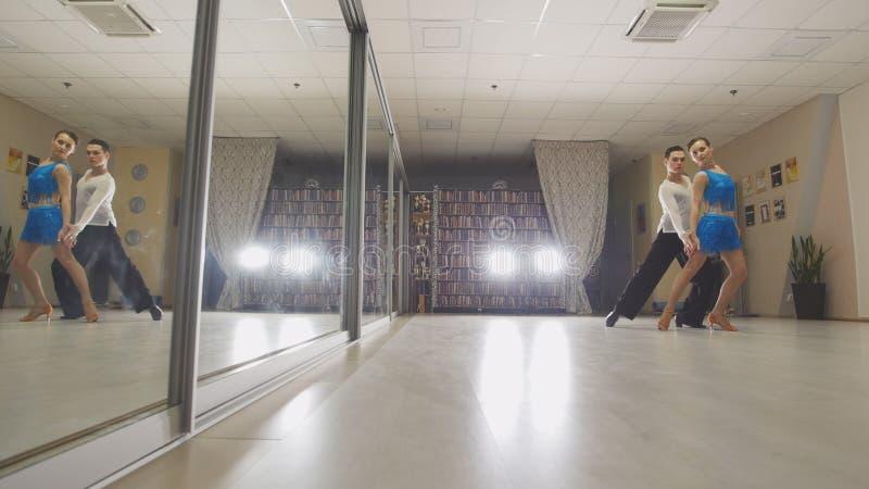 年轻有吸引力男人和妇女跳舞和在服装的实践的拉丁舞蹈在演播室 库存照片