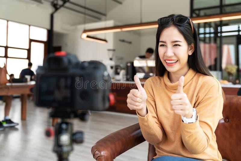年轻有吸引力的亚洲妇女博客作者或vlogger看照相机和谈话在录影射击在咖啡馆咖啡店 束起通信有概念的交谈媒体人社交 免版税库存图片