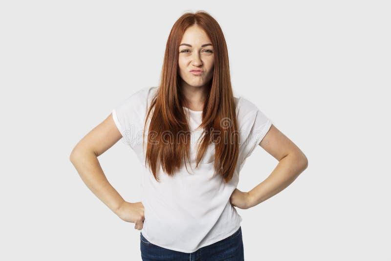 年轻有吸引力的在白色背景隔绝的红头发人欧洲妇女水平的画象站立用两手插腰她的手, 库存照片