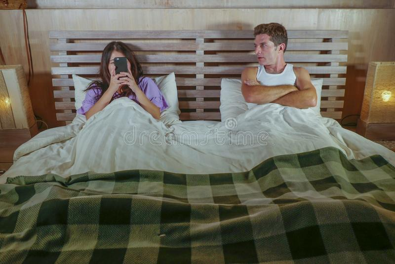 年轻有吸引力的夫妇在与使妇女上瘾使用互联网手机忽略被挫败的社会媒介的床上和喜怒无常让烦恼的人 图库摄影