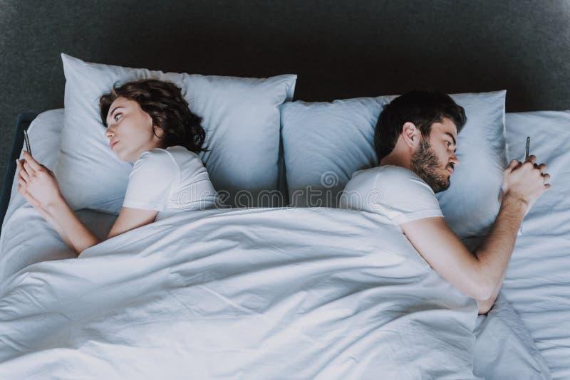 年轻有吸引力的夫妇有问题在床 库存图片
