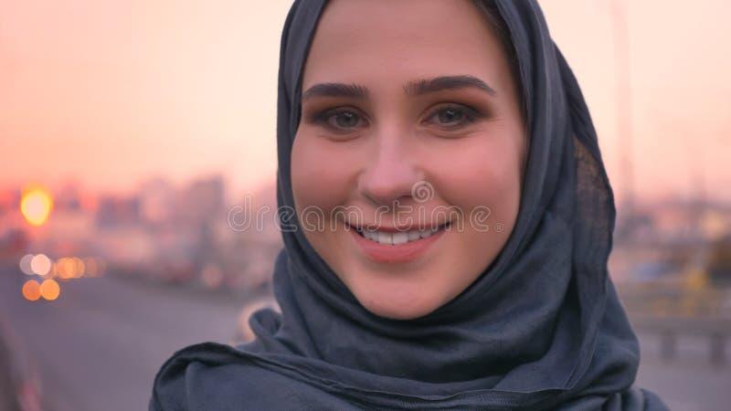 年轻有吸引力的女性面孔特写镜头射击在看直接照相机和微笑与在的城市布局的hijab的 免版税库存照片