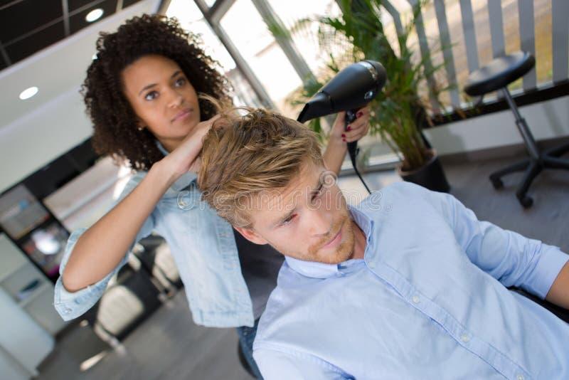 年轻有吸引力的妇女美发师发型顾客采撷 库存图片
