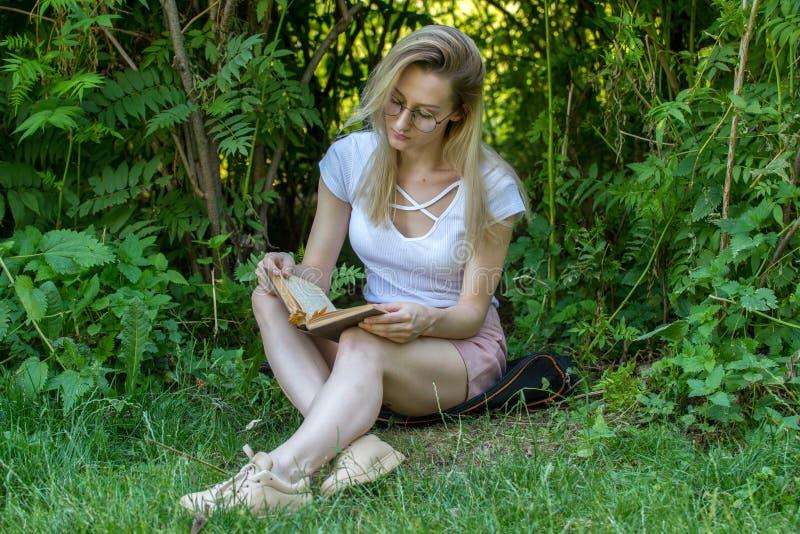 年轻有吸引力的妇女阅读书在树下在公园晴天 免版税库存照片