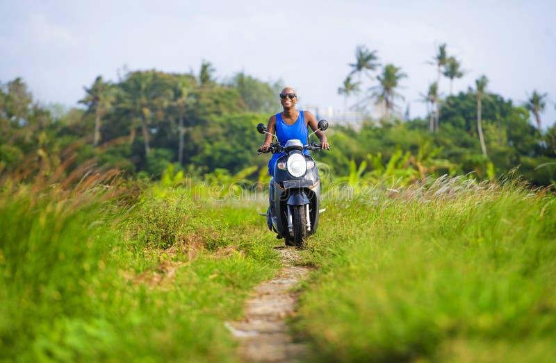 年轻有吸引力的旅游美国黑人的黑人妇女骑马摩托车愉快在沿绿色米的美丽的亚洲乡下调遣 免版税库存照片