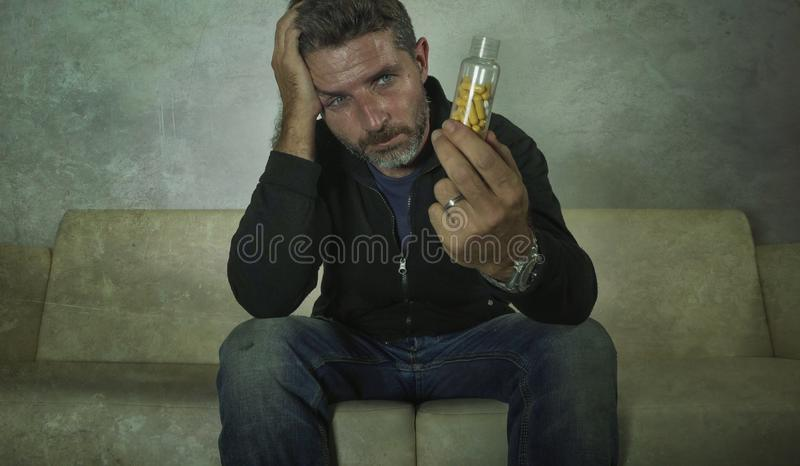 年轻有吸引力的沮丧和被浪费的药片剧烈的画象使人上瘾抗抑郁剂压片瓶坐长沙发的藏品 库存图片