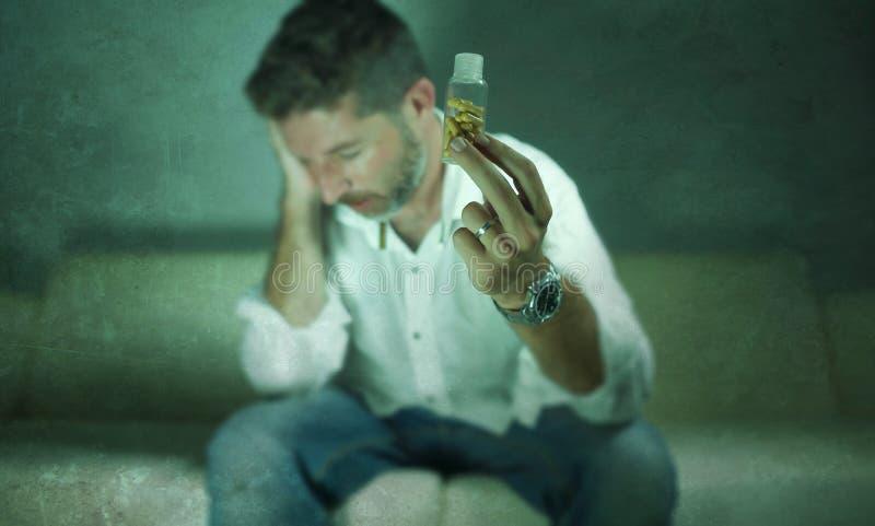 年轻有吸引力的沮丧和被浪费的药片剧烈的画象使人上瘾抗抑郁剂压片瓶坐长沙发的藏品 免版税库存图片