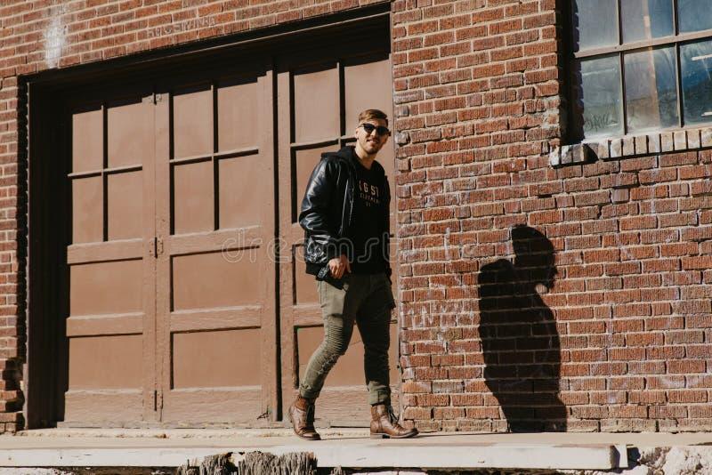年轻有吸引力的现代走,坐,微笑和笑在都市老被放弃的砖Wareh之外的时尚白种人男性人 免版税库存图片