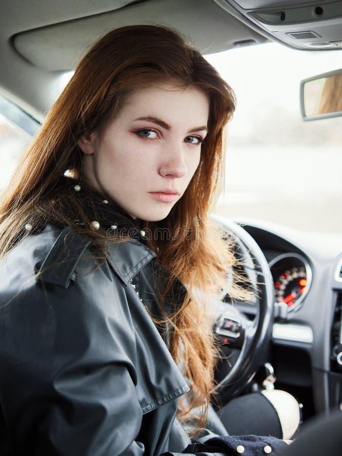 年轻有吸引力的红色回顾从驾驶席的头发自己经营的女商人司机接近的画象困住在a 免版税库存图片