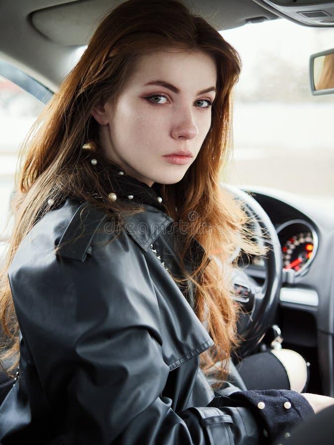 年轻有吸引力的红色回顾从驾驶席的头发自己经营的女商人司机接近的画象困住在a 免版税库存照片