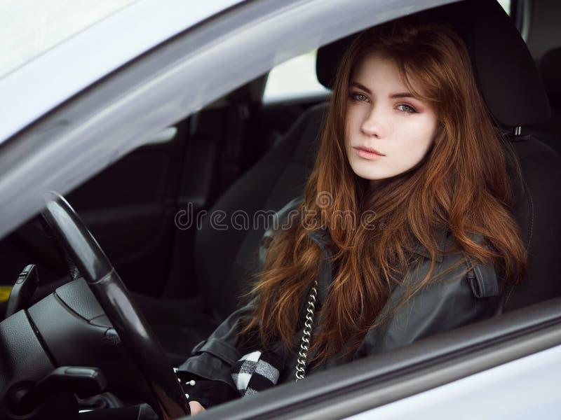 年轻有吸引力的红色坐在白色汽车的头发自己经营的女商人司机接近的画象困住在城市交通 库存图片
