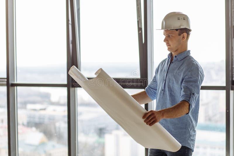 年轻有天赋的建设者看大厦透视计划  免版税库存照片