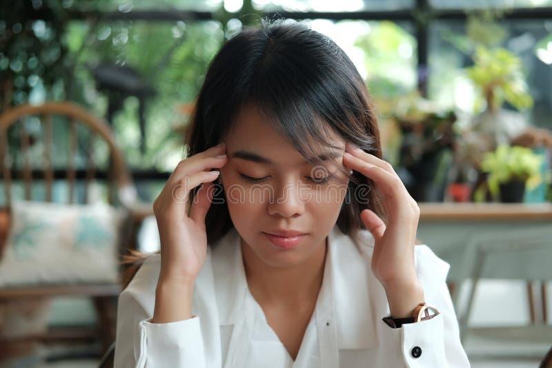 年轻有头疼和holdin的学生妇女佩带的白色衬衣 免版税库存照片
