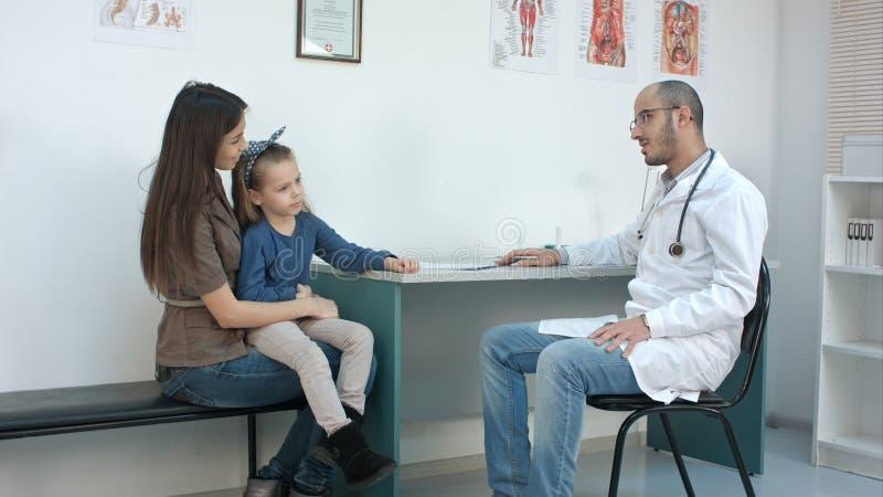 年轻有母亲和她逗人喜爱的小女孩与男性儿科医生的任命 库存图片