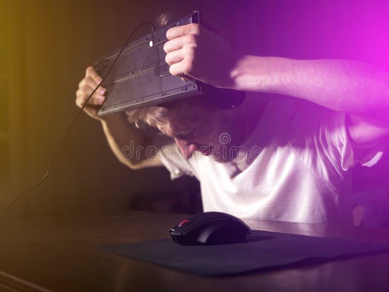 年轻有胡子的人变的疯狂疯狂和碰撞后打破键盘使用他的头在夜 库存图片