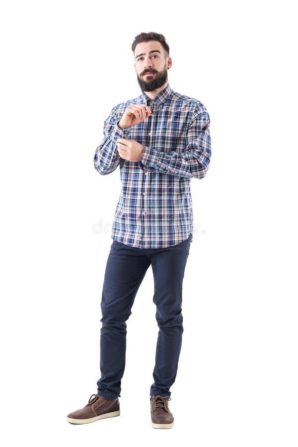 年轻有胡子的人换衣服按袖子按钮和确信地看照相机 免版税库存照片
