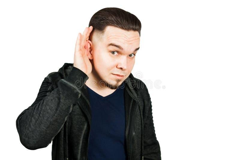 年轻有胡子的人窃听用手在耳朵 r 库存照片