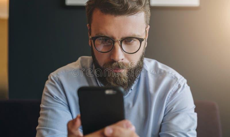 年轻有胡子的可爱的商人画象在衬衣和玻璃的使用智能手机,运作 行家人聊天 库存图片