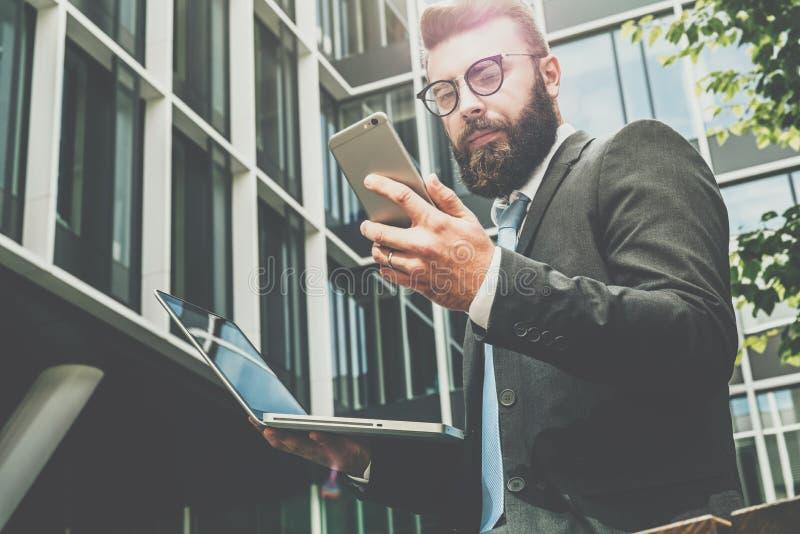 年轻有胡子的商人在他的手上站立反对现代大厦,使用智能手机并且拿着一台膝上型计算机 人工作 免版税库存照片