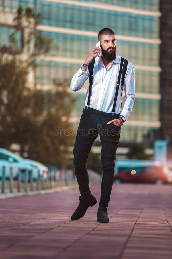 年轻有胡子的商人谈话在他的电话 免版税库存照片
