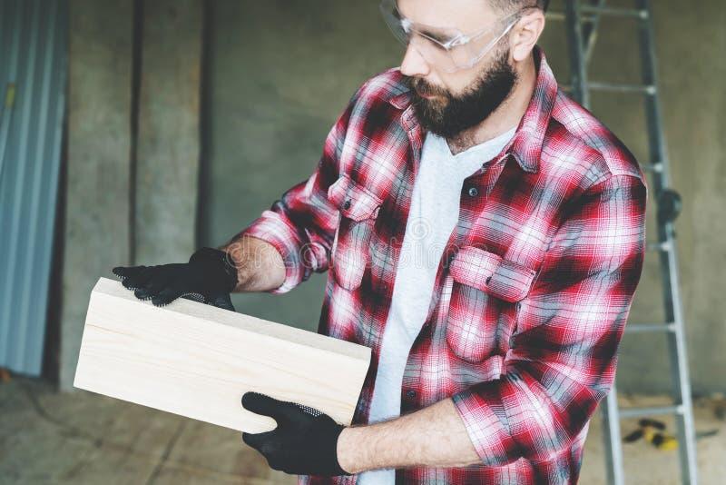 年轻有胡子的商人,建造者,安装工,木匠,建筑师,设计师在格子花呢上衣、玻璃和手套穿戴了 库存图片
