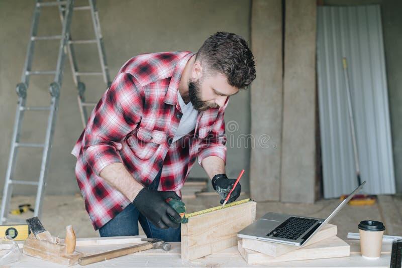 年轻有胡子的商人,建造者,安装工,木匠,建筑师,设计师,杂物工在格子花呢上衣穿戴了 免版税库存照片